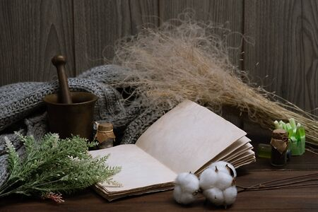 empty vintage notebook surrounded by herbs, alchemy appliances, potions mortar, feather and cotton bolls and ingredients on a dark wooden table. Magic alchemy and occultism. copy space for text. Stock Photo