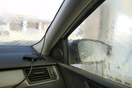 washing car in a self-service car wash station. Shooting from inside the car Stock Photo