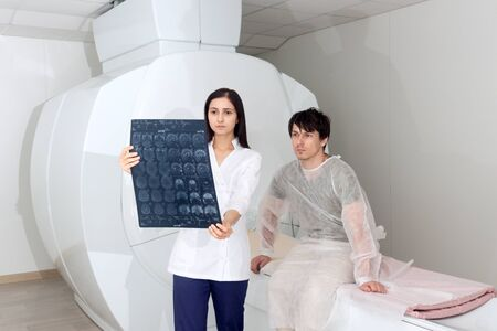 Confident pleasant female doctor working with MRI scan results and tells the patient the diagnosis. magnetic resonance imaging in a hospital Stock Photo