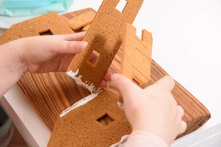 Mom glues the details gingerbread house with protein cream. female hands hold details close-up