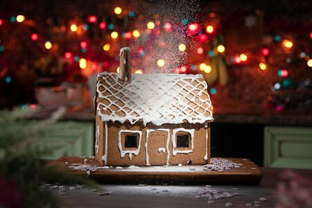 Gingerbread house sprinkled with icing sugar like snow. The spirit of Christmas. Garland on the background.