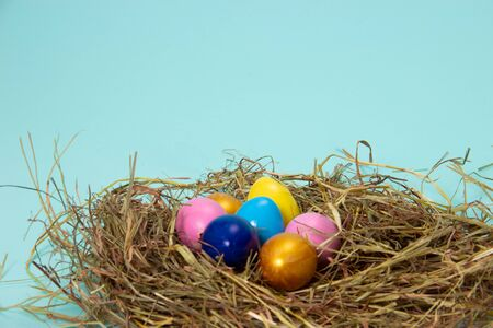colorful eggs in nest on hay in basket on blue background.