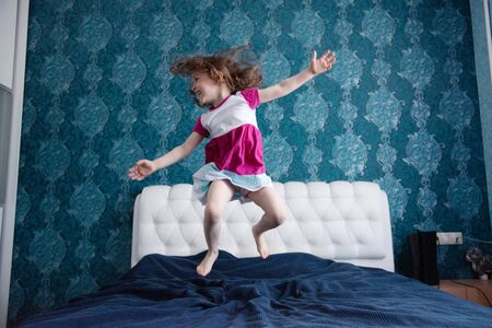 Active toddler girl dancing in bed baby jumping on white and blue bed blur background. what to do in quarantine. Archivio Fotografico
