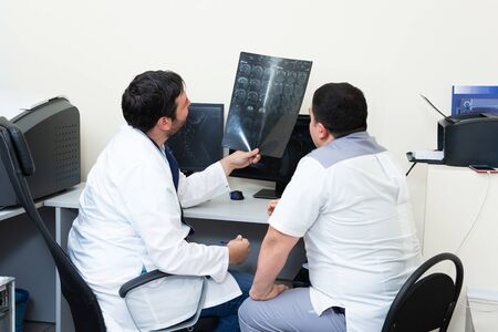 Two young doctors looking at patient's brain scanning. Medical consultation discuss MRI image. Archivio Fotografico