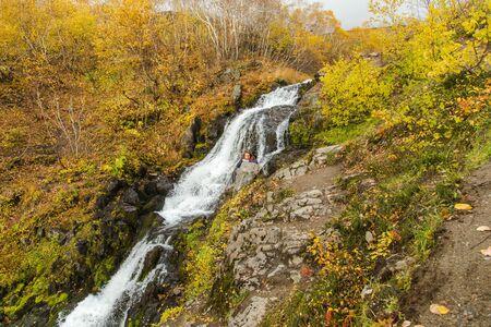 River in mountains, rocks in water. Beautiful golden autumn landscape in Kamchatka near Vachkazhetz volcano, Russia