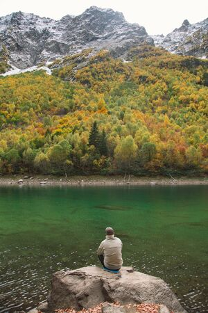 Traveling male tourist is sitting on the big boulder by the Baduk lake in Dombay mountains, Russia
