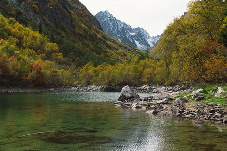 Serene fall landscape with turquoise Baduk lake in mountains in Dombay national park, Caucasus, Russia. Beautiful autumn landscape background.