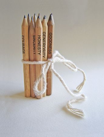 photomontage:  Photomontage depicting a group of wooden pencils tied together. Pencils are written on some human qualities