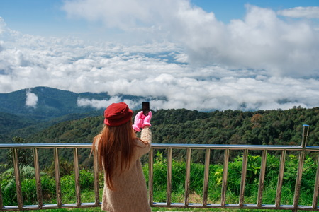 thai stretch: Woman hiker taking photo with cellphone at mountain