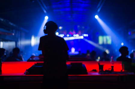 concert lights: Blurred background : Club, disco DJ playing and mixing music for crowd of happy people. Nightlife, concert lights, flares