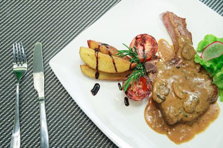 baked potatoes: Grilled Pork steaks, baked potatoes and vegetable salad.