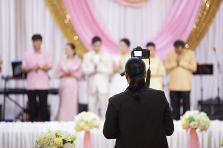 Cameraman recording video of  Wedding  out of focus,blur background. Stock Photo