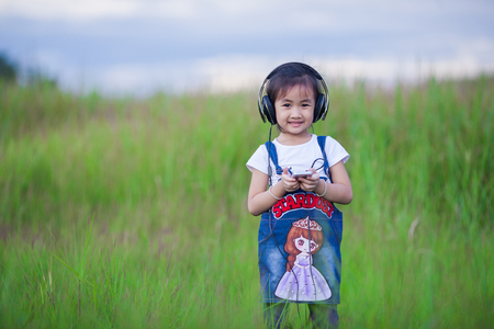 Children, technology and leisure concept - girl with headphones lying on natual and listening to music . Stock Photo