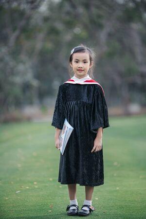 Asian cute child girl graduate. Girl smile on graduation kindergarten uniform.