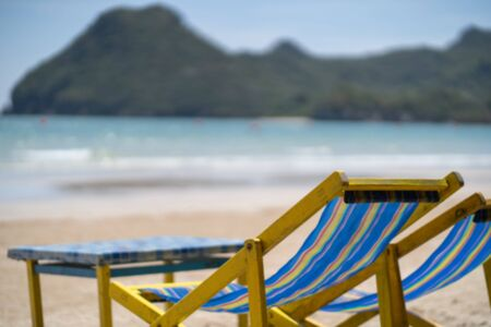 Blurry blackground Chairs on the tropical beach near sea, Thailand. Holidays Background