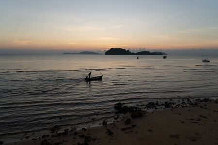 The beautiful landscape of fishing boat floating on sea with sunset blackground,thailand. Stock Photo