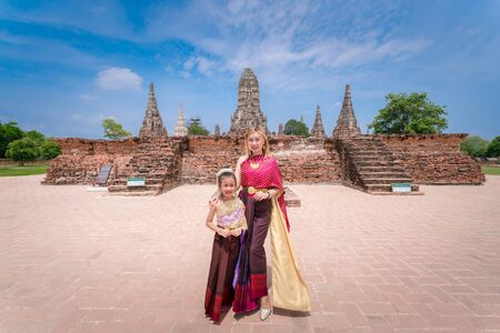 The family is wearing Thai clothes in old temple, Thailand grand palace. Ayutthaya Thailand. Ayutthaya famous sightseeing plac.