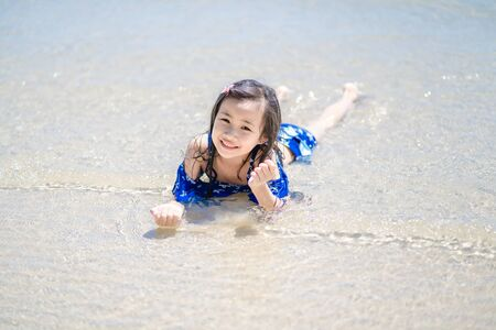 Children playing sand in summer on the beach.