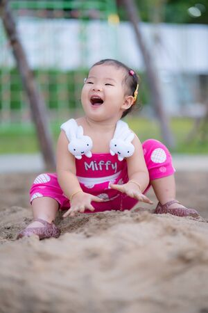 Happy kid girl playing sand having fun the natural park.