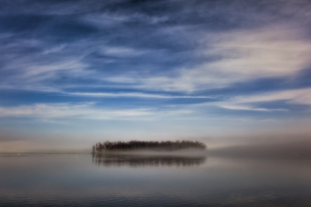 Island on a calm lake on a misty morning photo