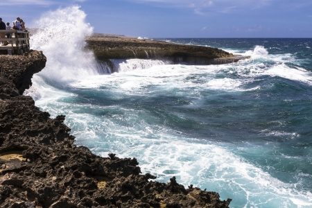 stormy waters: Group of people watching the big waves spraying cascades of water over volcanic cliffs  Costa Tabla, Northern shore of Curacao Stock Photo