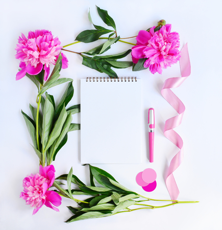 Album, pink peonies, camera, ribbon, pen and stickers on white background. Flat lay. Mock up for art work 写真素材