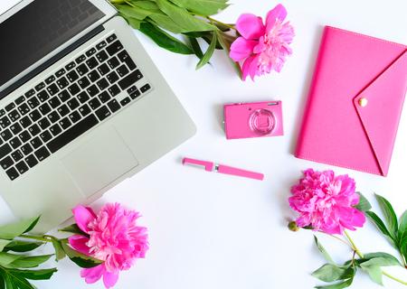 Ordinateur portable, pivoines et objets de travail roses sur fond blanc. laïque plat du lieu de travail