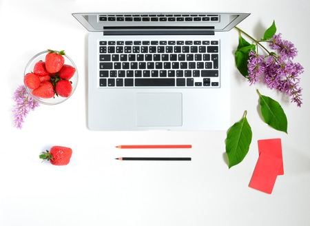 Laptop, lilac flowers bouquet, strawberry and pencil on white background. Flat lay of working place Stock Photo