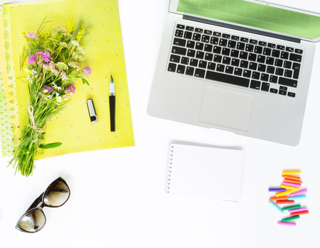 Laptop, bouquet of wildflowers, pen notebook, and sunglasses on white background. Flat lay of summer working place