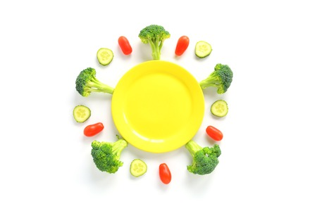Broccoli, tomatoes and cucumbers with plate. Top View isolated on white background. Vegetarian flat lay.