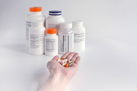 Group of supplement bottle and hand with pills on a white background. Pharmaceutical composition for templates, posters with text place.