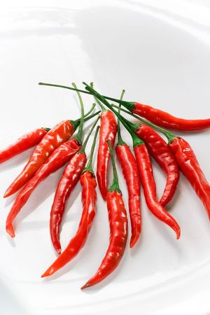 pungent: Hot Red Peppers on Shiny White Plate Stock Photo