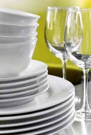 瀬戸物: 白い商業プレート、ボウル、緑色の背景でぼやけたワイングラス