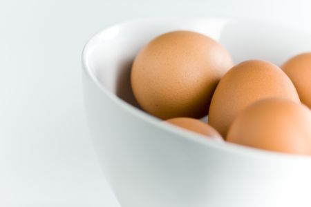 product range: Brown Eggs in Tilted White Bowl with Shallow Depth of Field
