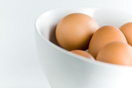 gamme de produit: Brown oeufs dans Tilted White Bowl avec profondeur de champ
