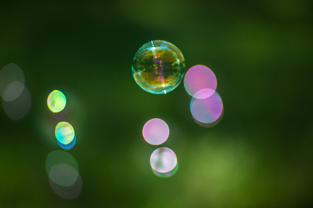Focused soap bubble with several defocused soap bubbles showing bokeh highlights