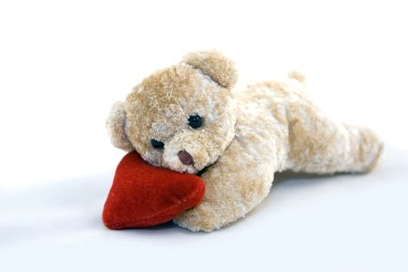Teddy bear with hear lying on white background