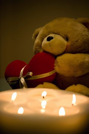 Valentines Teddy bear holding a heart behind the candles photo