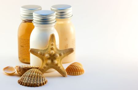 Three bottles with cosmetics and sea shells Stock Photo