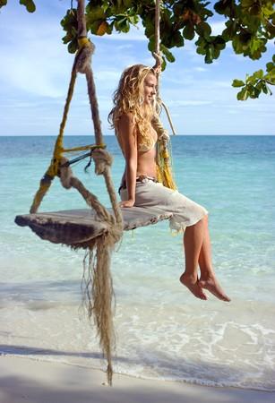 Girl sitting on rope swings on the beach