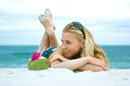 likeable: Cute girl with coconut lying on the beach