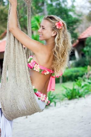 Blond girl sitting in hammock on sandy beach photo