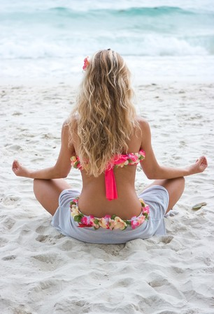 Blond girl sitting in lotos position on the beach Stock Photo
