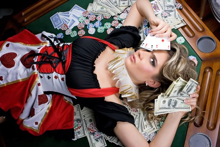 Poker girl lying on chips and money