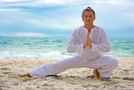 shu: Young man practising wushu on the sandy beach