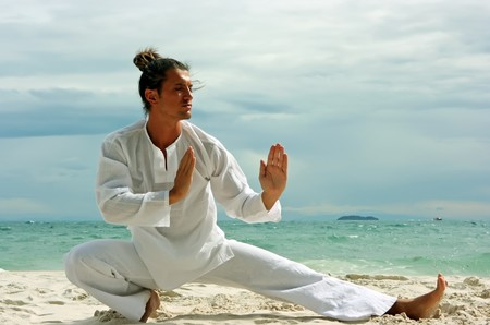 Young man practising wushu on the sandy beach