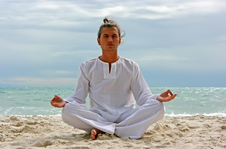 Young man practising yoga on the sandy beach photo