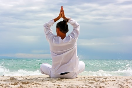 shu: Young man practising yoga on the sandy beach