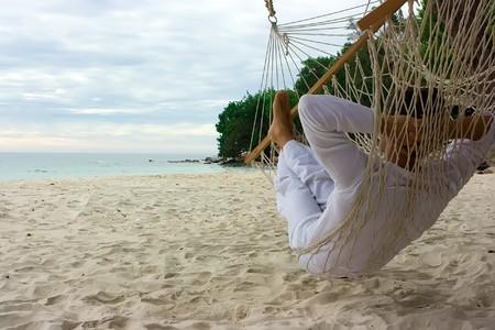 hamac: Un jeune homme de d�tente sur la plage de sable Banque d'images