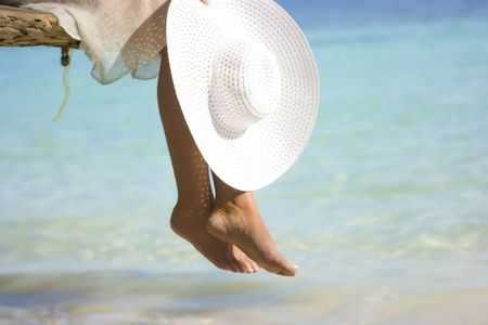 Girl sitting on the beach tree overwhelming the waters with white hat